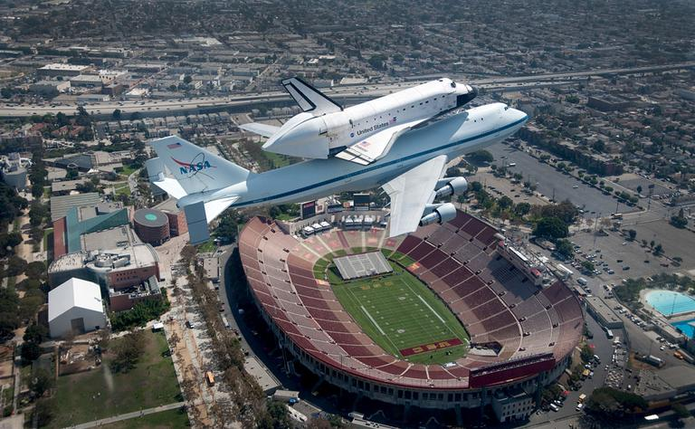 The space shuttle Endeavour atop the 747 shuttle carrier aircraft is seen flying over the LA Coliseum in Los Angeles during the final portion of its tour of California, Friday, Sept. 21, 2012. (AP Photo/NASA, Jim Ross)