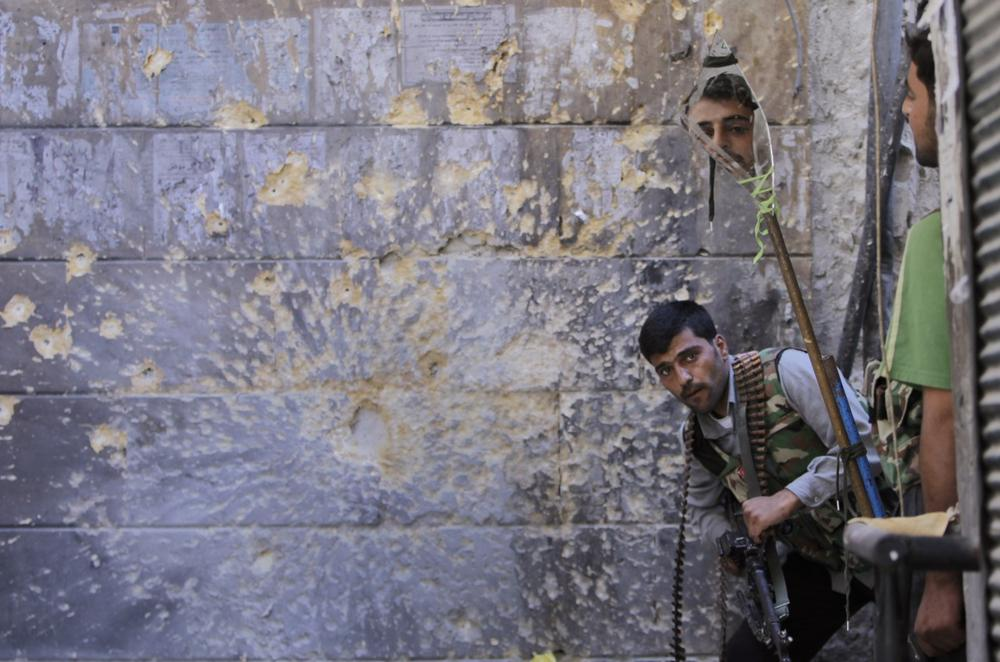 A Free Syrian Army soldier, right, looks through a mirror which helps him see Syrian troops from the other side, as he takes his position with his comrade during fighting, at the old city of Aleppo city, Syria, Monday Sept. 24, 2012. (AP Photo/Hussein Malla)