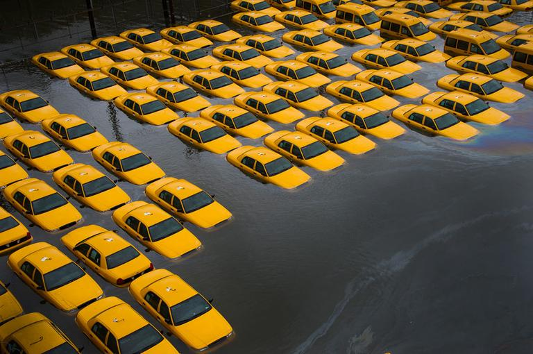 A parking lot full of yellow cabs is flooded as a result of superstorm Sandy in Hoboken, NJ. Oct. 30, 2012. (AP Photo/Charles Sykes)