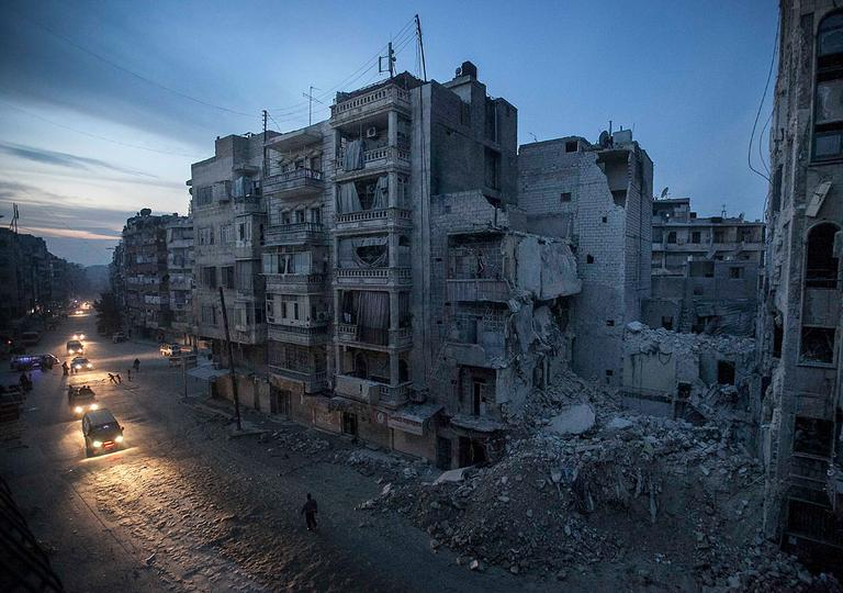Night falls on a Syrian rebel-controlled area as destroyed buildings, including Dar Al-Shifa hospital, are seen on Sa'ar street after airstrikes targeted the area, killing dozens in Aleppo, Syria. Nov. 29, 2012. (AP Photo/Narciso Contreras)