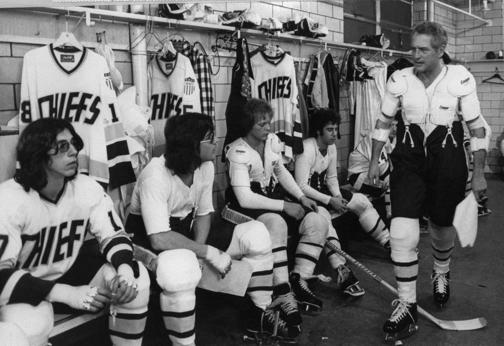 Paul Newman, (r) in the role of Charlestown Chiefs coach Reggie Dunlop, addresses his team, including two of the three Hanson brothers (in glasses). This year marks the 35th anniversary of 'Slap Shot'. (AP)