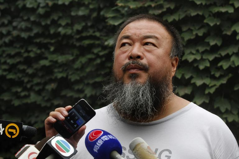 Dissident artist Ai Weiwei listens as his lawyer announces over a speakerphone the verdict of Ai's lawsuit against the Beijing tax authorities in Beijing Friday, July 20, 2012. A Beijing court on Friday rejected an appeal by Ai against a more than $2 million fine for tax evasion, which he says is part of an intimidation campaign to stop him from criticizing the government. (AP)