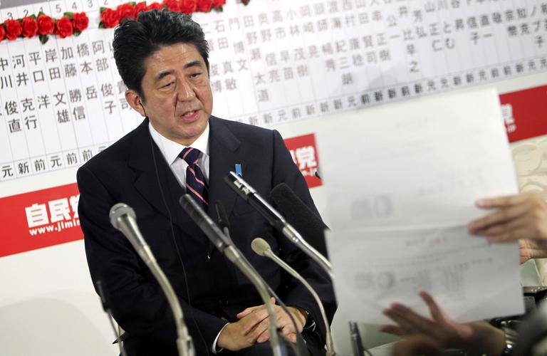 Japan's main opposition Liberal Democratic Party leader Shinzo Abe answers a reporter's question at the party headquarters in Tokyo on Sunday night. The conservative LDP stormed back to power in parliamentary elections Sunday after three years in opposition, signaling a rightward shift in the government that could further heighten tensions with rival China. (Junji Kurokawa/AP)