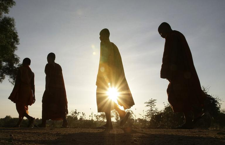 Cambodian Buddhist monks are silhouetted as they walk at the outskirt of Phnom Penh, Cambodia, Tuesday, Dec. 18, 2012. (Heng Sinith/AP)
