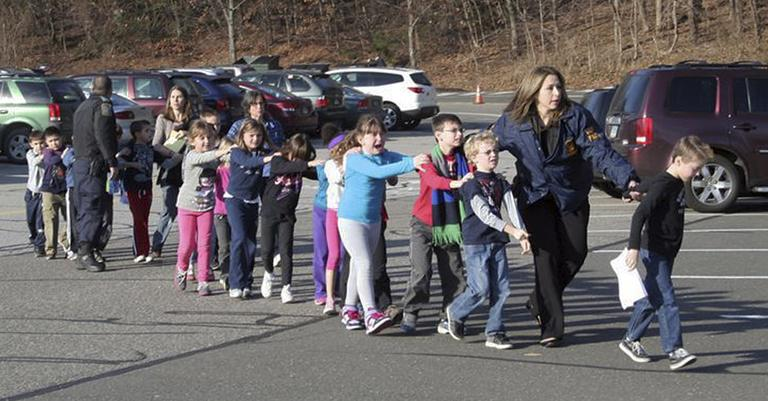 Connecticut State Police lead children from the Sandy Hook Elementary School in Newtown, Conn., following a reported shooting there Friday, Dec. 14, 2012. (AP Photo/Newtown Bee, Shannon Hicks)