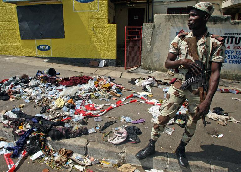 An Ivory Coast soldier stands next to the belongings of people involved in a deadly stampede in Abidjan, Ivory Coast, Tuesday, Jan. 1 2013. (Emanuel Ekra/AP)