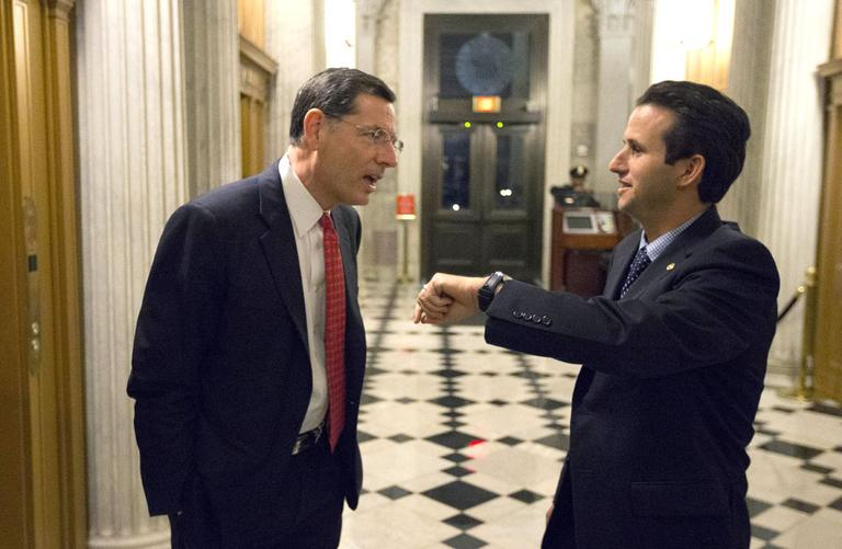 Sen. John Barrasso, left, R-Wyo., talks with Sen. Brian Schatz, D-Hawaii, who holds up his watch, near the Senate chambers after a vote on the fiscal cliff, on Capitol Hill Tuesday, Jan. 1, 2013 in Washington. (AP/Alex Brandon)