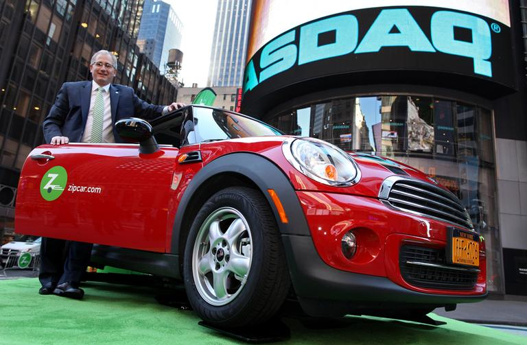 The boards of Zipcar and Avis unanimously approved the $491.2 million buyout. Here, Zipcar Chairman and CEO Scott Griffith stands with a Zipcar Mini-Cooper before the opening bell at the NASDAQ Market Site in New York in 2011. (AP Photo/Zipcar.com, Craig Ruttle, File)