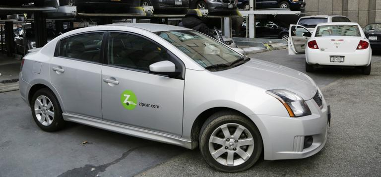 Avis is buying Zipcar for $491.2 million, expanding its offerings from traditional car rentals to car sharing services. Pictured here is a a Zipcar is parked at a lot in New York on Wednesday, Jan. 2, 2013. (Mark Lennihan/AP)
