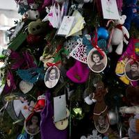 Portraits of slain students and teachers hang from a tree at a memorial in Newtown, Conn. Tuesday, Dec. 25, 2012. (AP/Craig Ruttle)
