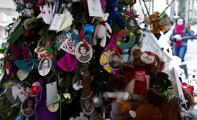 Portraits of slain students and teachers hang from a tree at a memorial in Newtown, Conn., Dec. 25, 2012. (Craig Ruttle/AP)