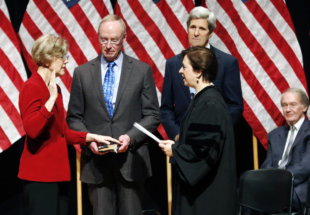 Supreme Court Justice Elena Kagan administers the oath of office to Sen. Elizabeth Warren as Warren's husband, Bruce Mann, holds a bible during a re-enactment of Warren's Senate swearing-in ceremony at Roxbury Community College Saturday. (Michael Dwyer/AP)
