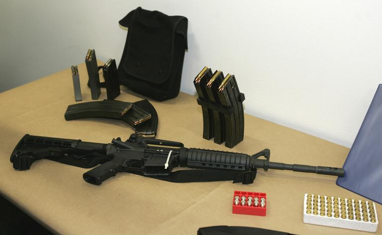 This 2006 file photo shows a Bushmaster AR-15 semi-automatic rifle and ammunition on display at the Seattle Police headquarters in Seattle. A similar rifle was used in the Newtown school massacre. (Ted S. Warren/AP)