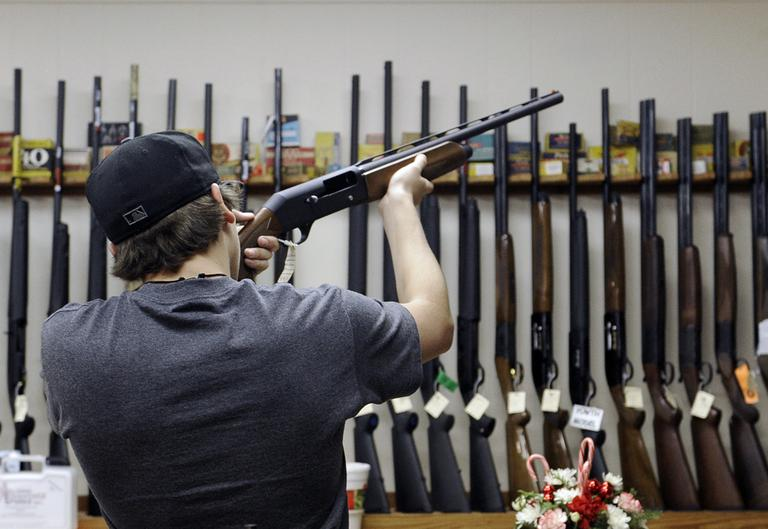 In this Wednesday, Dec. 19, 2012 file photo, a customer checks out a shotgun at Burdett & Son Outdoor Adventure Shop in College Station, Texas. (Pat Sullivan/AP)