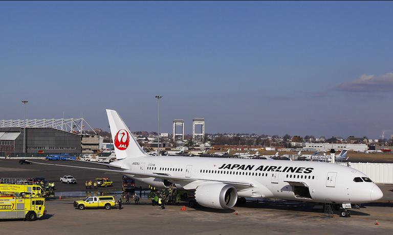 A Japan Airlines Boeing 787 Dreamliner jet aircraft is surrounded by emergency vehicles after a small electrical fire filled the cabin of the with smoke about 15 minutes after it landed at Logan Airport on Jan. 7, 2013. (Stephen Savoia/AP)