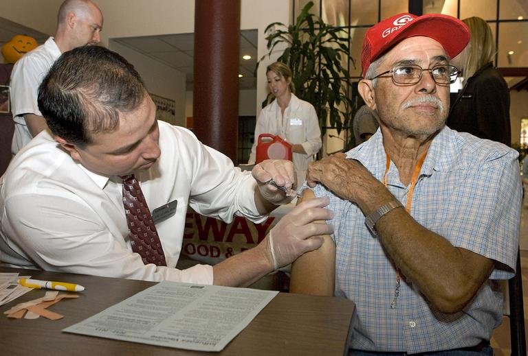 Jesus Ortiz, right, gets his flu shot from Joe Leyba, left, during a flu shot clinic at the Armory Park Senior Center in Tucson, Ariz., in October 2012. (John Miller/AP/NCOA)