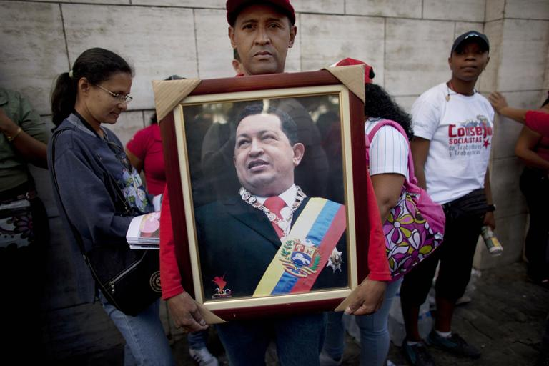 A supporter of Venezuela's President Hugo Chavez poses for a portrait as he holds a photograph of Chavez outside the National Assembly in Caracas, Venezuela on Saturday. (Ariana Cubillos/AP)