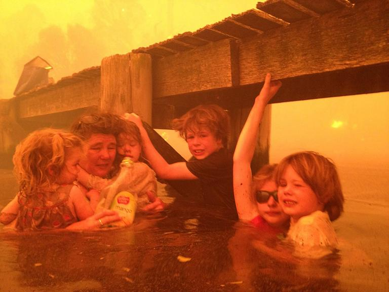 In this Jan. 4, 2013, photo provided by the Holmes family, Tammy Holmes and her grandchildren take refuge under a jetty as a wildfire rages nearby in the Tasmanian town of Dunalley, east of the state capital of Hobart, Australia. The family credits God with their survival from the fire that destroyed around 90 homes in Dunalley. (Tim Holmes/AP)