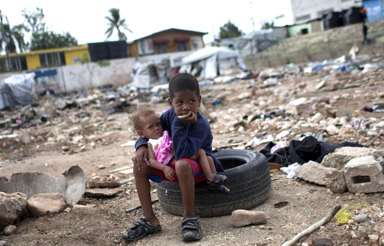 Six-year-old Charles Kerby hold his 11-month-old sister Mikerlina Dragon inside the Ste Therese camp, set up for people displaced by the 2010 earthquake, in Petion-Ville, Haiti, in June 2012. Kerby had to drop out of school after the 2010 earthquake to help his working mother care for his two brothers and sisters. (Dieu Nalio Chery/AP)
