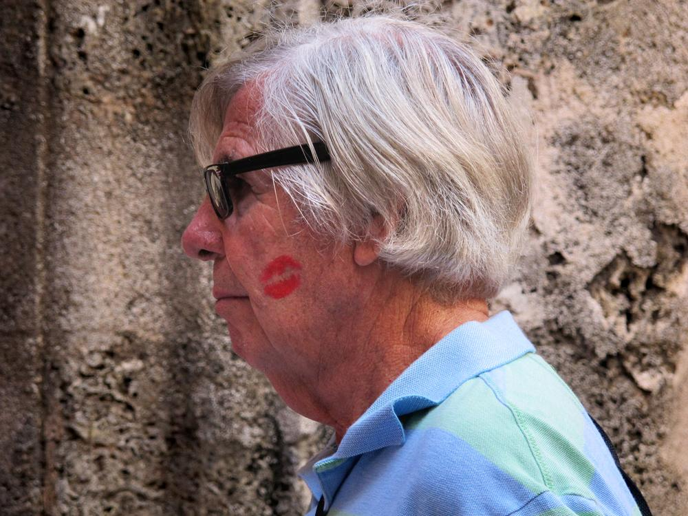 American art collector Tom Licciardi bought a big, red kiss from a Cuban woman in Havana's San Francisco Square. Cubans have licenses to sell many things to tourists, including smooches.