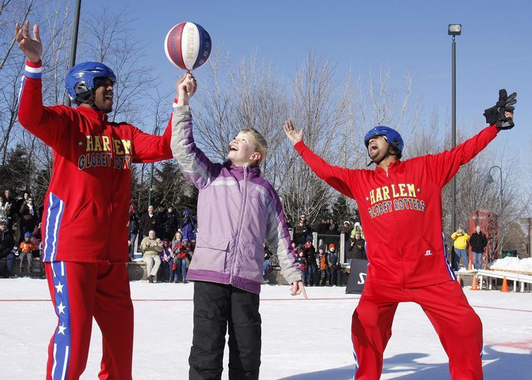 Emilee Bogda, 10, learns some tricks from Globetrotters Scooter Christensen (l) and Handles Franklin. (William Pugliano/Harlem Globetrotters/AP)