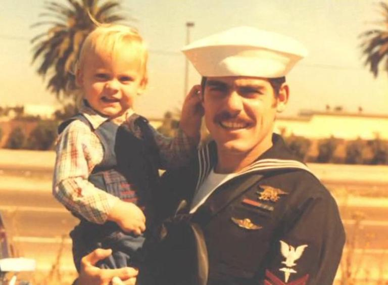 Rob Guzzo is pictured as a child, being held by his father, Bob Guzzo, also a Navy SEAL. (Screenshot from The Fold)