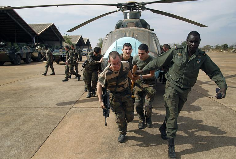 Malian soldiers helped by French troops, move a broken helicopter out a hangar to make room for more incoming troops at Bamako's airport on Tuesday. French forces led an all-night aerial bombing campaign Tuesday to wrest control of a small Malian town from armed Islamist extremists. (Jerome Delay/AP)