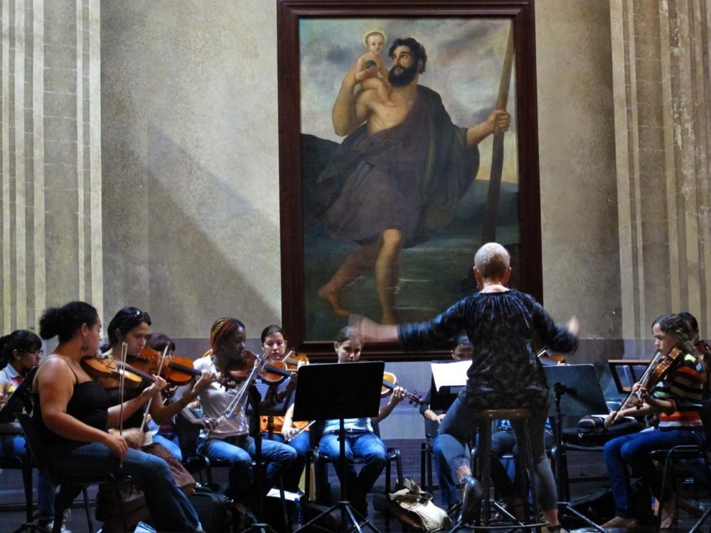 Cuban conductor Zenaida Romeu rehearsing with her all-female orchestra Camerata Romeu in Old Havana's Basilica of St. Francis of Assisi. (Andrea Shea/WBUR)