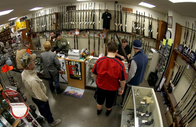 In this photo made with a fisheye lens, customers line up at the gun counter at Duke's Sport Shop on Tuesday in New Castle, Pa. (Keith Srakocic/AP)