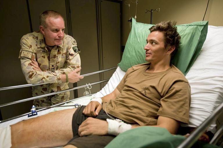 In this undated photo provided by Maj. Gen. John Cantwell, left, the general talks with an unidentified injured man at an undisclosed location in Afghanistan. Maj. Gen. Cantwell, the former commander of Australia's troops in Afghanistan, spent 20 years secretly suffering from PTSD, which began after he served in the Gulf War and grew worse as he rose through the military's ranks. (Sgt. Neil Ruskin/AP)