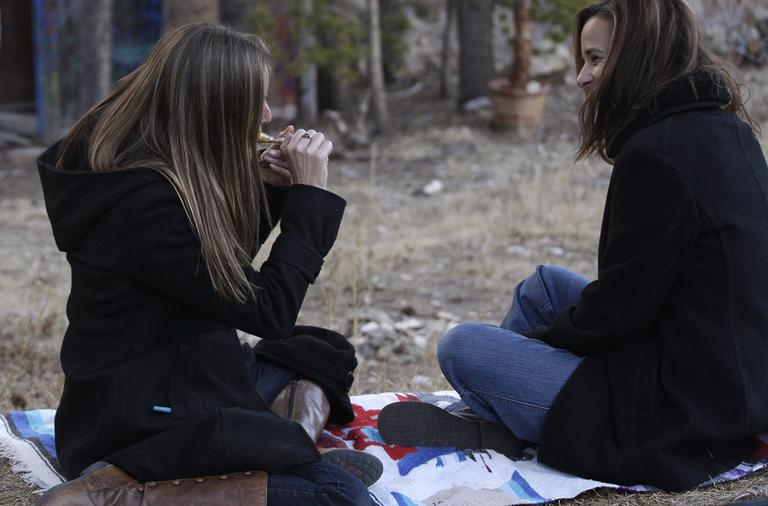 In this November 2012 photo, two women smoke marijuana together, behind a home in the woods near the small Rocky Mountain town of Nederland, Colo. (Brennan Linsley/AP)
