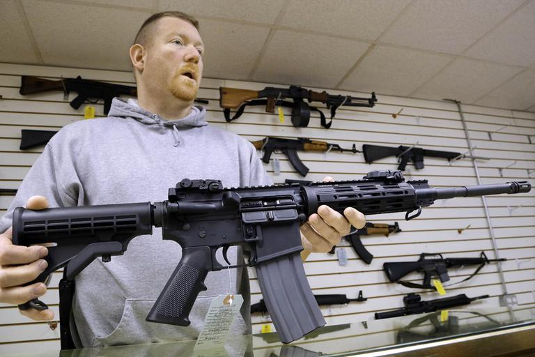 John Jackson, co-owner of Capitol City Arms Supply, holds an AR-15 rifle for sale at his business in Springfield, Ill. on Wednesday. (Seth Perlman/AP)