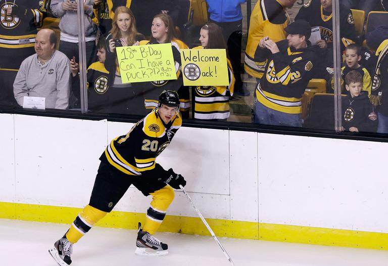 The Bruins' Daniel Paille skates past fans holding signs at Boston's TD Garden before a scrimmage on Tuesday. (Elise Amendola/AP)