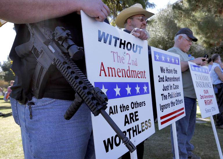 Gun rights supporters stand outside the Capitol Sat, Jan. 19, 2013 in Phoenix during a Guns Across America rally. (Matt York/AP)