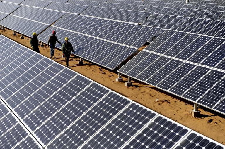 In this November 2010 photo released by China's Xinhua News Agency, workers check on solar panels in Yulin, northwest China's Shaanxi Province. (Liu Xiao/Xinhua/AP)
