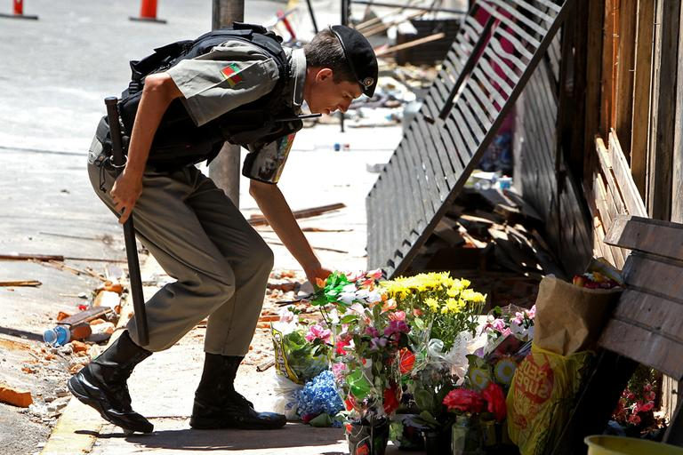 A police officer places flowers outside the Kiss nightclub that were brought by mourners in memory of those who died due to a fire at the club in Santa Maria, Brazil, on Monday. (Nabor Goulart/AP)