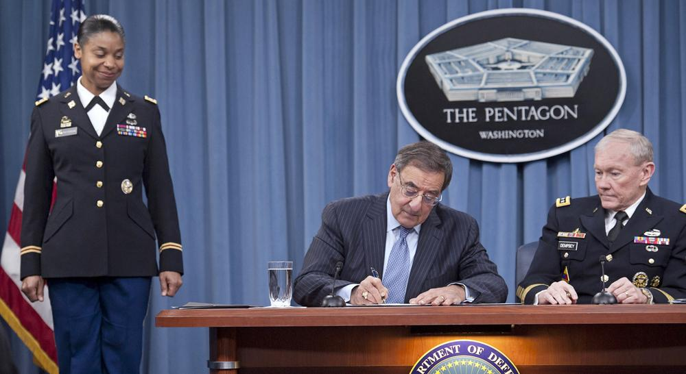Defense Secretary Leon Panetta, flanked by Joint Chiefs Chairman Gen. Martin Dempsey, right, and Army Lt. Col. Tamatha Patterson, signs a memorandum ending the 1994 ban on women serving in combat roles in the military, Thursday, Jan. 24, 2013. (Cliff Owen/AP)