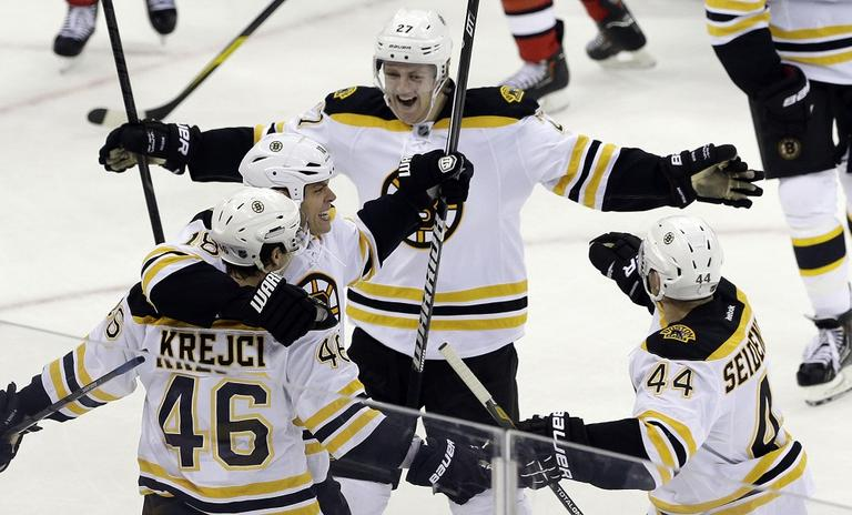 Bruins' David Krejci (46) is congratulated by Nathan Horton, Dennis Seidenberg (44), of Germany, and Dougie Hamilton (27) after Krejci scored the game winning goal against the Carolina Hurricanes. (Gerry Broome/AP)