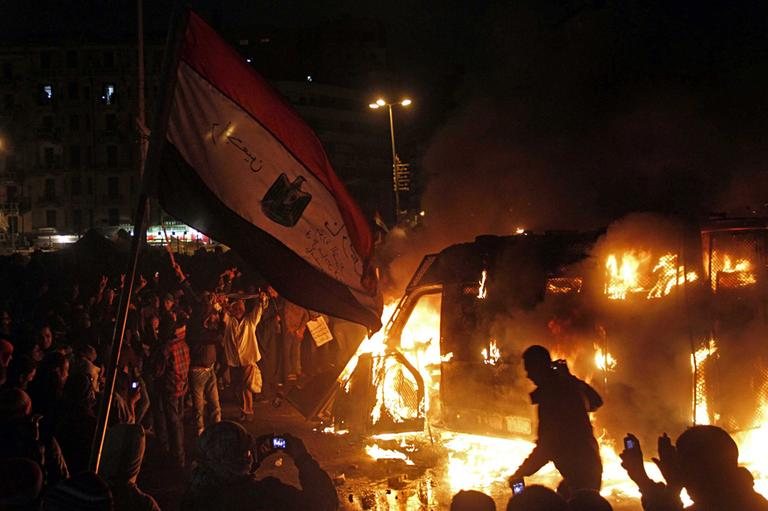 Egyptian protesters use camera phones on Monday to capture a burning state security armored vehicle that demonstrators commandeered during clashes with security forces nearby and brought to Tahrir Square and set it alight, in Cairo, Egypt. (Mostafa El Shemy/AP)