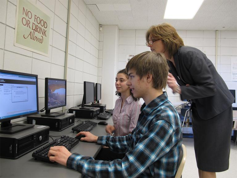 Jonathan Flatley and Joclyn Crivello are taking an AP physics course online. Milford High School Vice Principal Carolyn Banach offers support. (Monica Brady-Myerov/WBUR)