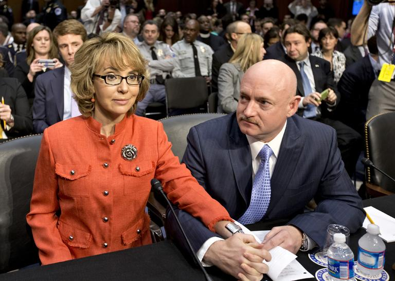 Former Arizona Rep. Gabrielle Giffords, who was seriously injured in the mass shooting that killed six people in Tucson, Ariz. two years ago, sits with her husband, Mark Kelly, right, a retired astronaut, on Wednesday, prior to speaking before the Senate Judiciary Committee. (J. Scott Applewhite/AP)