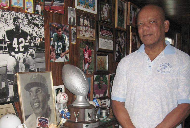 Butch Byrd stands in front of memorabilia in his Westborough home. (Lynn Jolicoeur/WBUR)