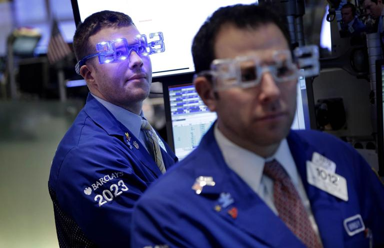 """Traders wear """"2013"""" glasses as they work on the floor at the New York Stock Exchange in New York. (AP)"""