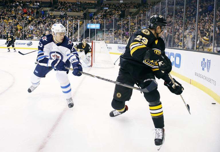 Boston Bruins' Chris Kelly, right, sends the puck behind the net next to Winnipeg Jets' Alexei Ponikarovsky, of Ukraine, during the first period of an NHL hockey game in Boston, Monday, Jan. 21, 2013. (AP Photo/Michael Dwyer)