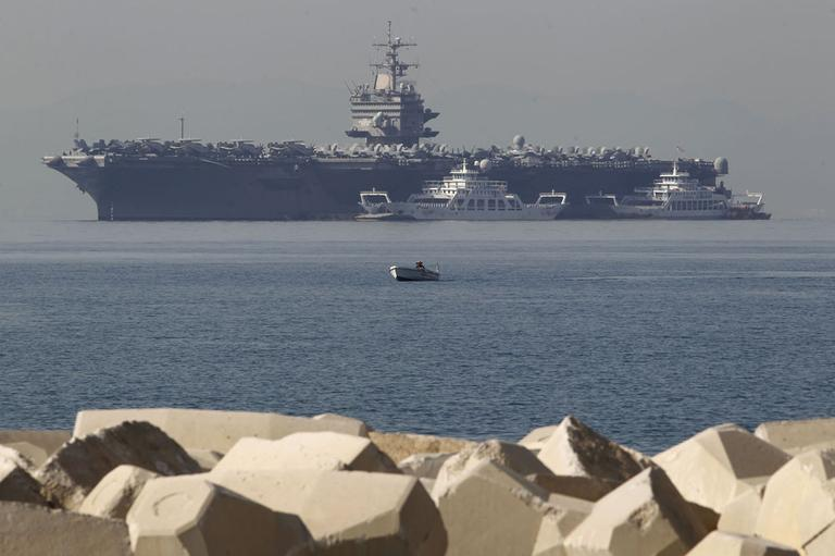 A small boat passes in front of the aircraft carrier USS Enterprise anchored of the coast of Faliro, near Athens. (AP)