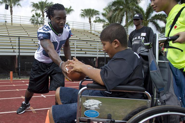 Seattle Seahawks football player Kennard Cox hands the football off to Juan Herrera during the fifth annual 12th Man Football Cheer Camp in Miami Lakes, Fla., Saturday, Feb. 25, 2012. The 12th Man Football Cheer Camp was created by Miami Dade police officer Allen Lowy to give those with special needs or disabilities the opportunity to be a part of organized football. (AP)