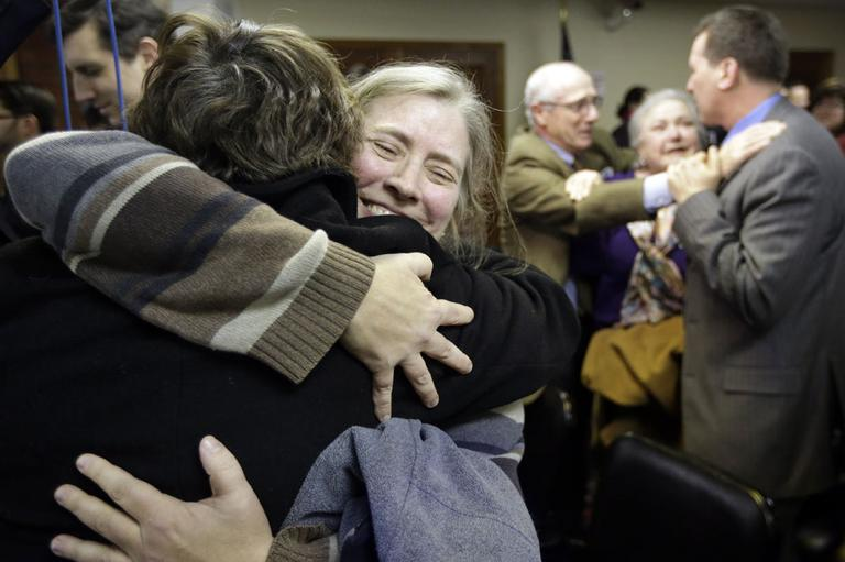 C. Kelly Smith, of Providence, R.I., center, a member of Marriage Equality Rhode Island, hugs fellow member Wendy Becker, left, also of Providence, after a house committee vote on gay marriage at the Statehouse, in Providence, Tuesday, Jan. 22, 2013. (AP)