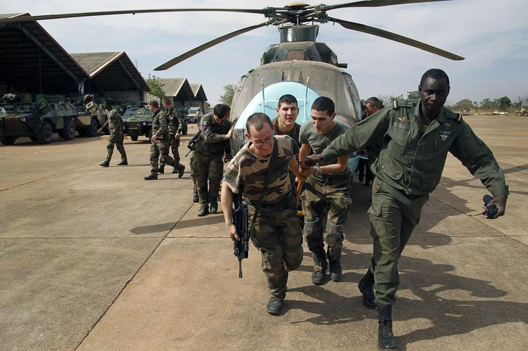 Malian soldiers helped by French troops, move a broken helicopter out a hangar to make room for more incoming troops at Bamako's airport Tuesday Jan. 15. 2013. (AP)