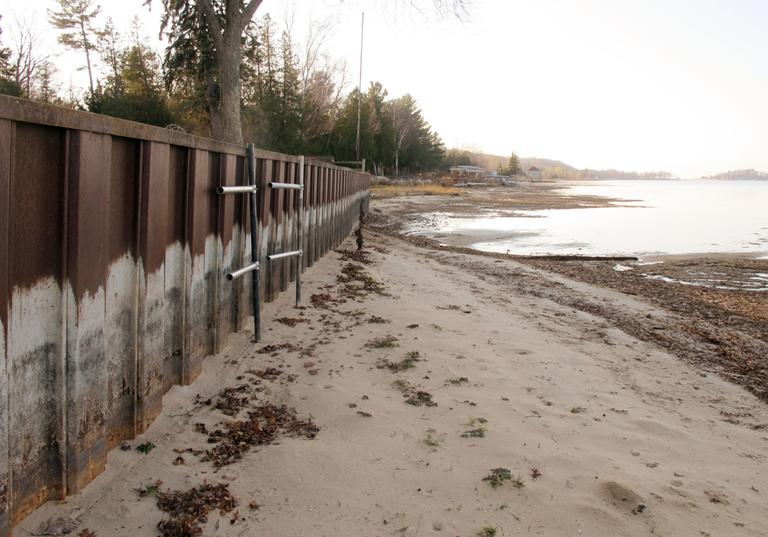 In this Nov. 16, 2012 photo, the white streaks on a steel breakwall show the normal water level on Portage Lake at Onekama, Mich., which is connected by a channel to Lake Michigan. Levels across much of the Great Lakes are abnormally low, causing problems for small harbor towns that rely on boating and water tourism. (John Flesher/AP)