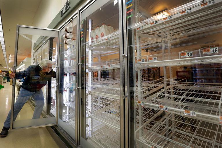Jack Percoco, of Cambridge, reaches into depleted shelves for milk at a supermarket in Somerville Friday. (Elise Amendola/AP)